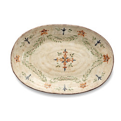 Medici Large Oval Platter - Beautifully sprigged with green, rust, and indigo forming classic Italianate patterns on a cream-colored base, the Medici Large Oval Platter is painted across its curved surface so that whether you're serving on it or displaying it, the beauty and detail are superb. This platter was handmade in Italy, where the rich inspirations of the Renaissance suggested the warm colors and handsome design.