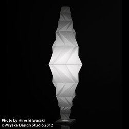Artemide - Artemide | Minomushi Floor Lamp - Design by Issey Miyake and Reality Lab.By Artemide.The IN-EI collection revolves around a fabric derived from entirely recycled materials, diffusing light in an extremely interesting way. The fiber is made using PET bottles, processed using innovative technology that reduces both energy consumption and CO2 emissions. Issey Miyake's artistic vision, combines new a 3D mathematical process with the Japanese tradition of light.Each lampshade is created using 2 or 3D mathematical principles, where the light and shade harmoniously alternate. Issey Miyake's unique folding technology creates both statuesque forms as well as sufficient solidity. The structure of the recycled material, together with an additional surface treatment allows these shades to perfectly keep their shape without the need for an internal frame. The shades can easily be stored flat when not in use.The Minomushi Floor Lamp features a recycled fabric shade with an internal frame made of a diffusing tube of extruded methacrylate, frosted both internally and externally. The internal part of tube is fitted with extruded aluminum serving as heat sync. Accented with white painted die-cast aluminum caps and a laser etched Artemide and IN-EI logo. Ships with 4 feet of cord with dimmer.