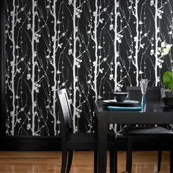"""Graham & Brown Solitude Wallpaper - When this wallpaper is hung it is like looking into an enchanted forest. The silhouettes of branch and trunk glistening mica on a black texture help create a feeling of inner calm and solitude. About Graham & Brown Founded in 1946 by friends Harold Graham and Henry Brown Graham & Brown has always been about brightening the home. From modest beginnings with surplus metallic paper and an embossing machine Graham & Brown has grown to include a range of products such as Superfresco - easy to hang and able to be painted or washed - and other """"""""paste the wall"""""""" products that allow homeowners greater ease in hanging wallpaper themselves. The company's product line today includes wall art paint and children's decor in addition to its famous wallpaper."""