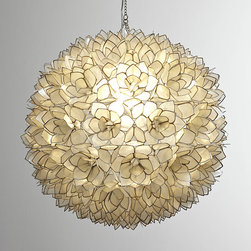 Capiz-Shell Pendant Light - Exclusively ours. Translucent capiz shells are fashioned into flowers and edged with silvery metal to form this breathtaking sphere. To display two as shown above the table, we cut the cords to the desired length and hardwired the pendants.