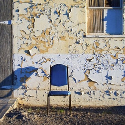 """""""Blue Chair, Death Valley Junction"""" Artwork - A single, blue chair in front of an abandoned building is a thought-provoking depiction of Death Valley Junction, a ghost town in California. Captured by photographer Jacquelyn Sloane Siklos, the haunting photograph is a stunning addition to any room in your home."""