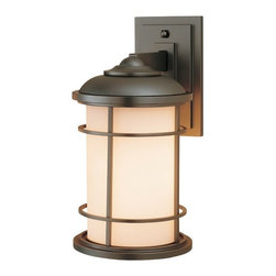 Feiss Lighting - 14-Inch Outdoor Wall Light - OL2201BB - This contemporary outdoor wall light was designed with the style of a lighthouse in mind. Mounted against the wall with a subtly stepped rectangular base, this sturdy fixture is constructed of die-cast zinc, with the bars of its shade's cage made of solid brass. The cream-colored glass contrasts well with the deep bronze finish, which is a triple-plated and powder-coated lacquer for durability and weather resistance. Measures 14 inches in height, extends 9 inches from the wall. Backplate measures 7-1/2 inches high by 4-1/2 inches wide. Takes (1) 100-watt incandescent A19 bulb(s). Bulb(s) sold separately. Wet location rated.