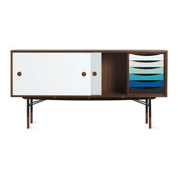 Onecollection - Finn Juhl Credenza - After studying at the famous Royal Danish Academy of Fine Arts in Copenhagen and working for architect Vilhelm Lauritzen, Finn Juhl set up his own design office in 1945. Later that year, Juhl and master cabinetmaker Niels Voder, collaborators since 1937, created a buzz at the Cabinetmakers' Guild exhibition with their expressive, sculptural pieces. In 1951, Juhl went on to make his stateside debut at the Good Design exhibit in Chicago and at MoMA in New York, and he represented Denmark in designing a meeting chamber at United Nations Headquarters. The trained architect and self-taught furniture designer drew the inspiration for his Finn Juhl Credenza (1955) from the cubist movement and Goethe's color wheel, reflected in the piece's simple geometric shapes and interlocking planes and its sliding doors and six trays finished in varying shades of blue lacquer. The left interior has two removable pegged shelves, the right an open compartment next to the one for the trays. Holding the walnut body, the hand-burnished steel frame with wooden feet lends the piece airiness. Ships fully assembled. Made in Denmark. DWR Exclusive