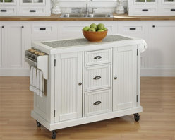 HomeStyles - Distressed White Kitchen Cart - Give your home a cozy, inviting atmosphere with the Nantucket Kitchen Cart. It's sanded worn edges and distressed white finish provides the casual elegance that's great for any home decor style. The Nantucket Kitchen Cart is constructed of hardwood solids and engineered wood. Finishing process includes paint specking on the sanded and distressed white finish providing a weathered look. Features include ���_ inch salt and pepper granite inset, two cabinet doors each containing an adjustable shelf, three storage shelves, built-in spice rack and towel bar, paper towel holder, and industrial size casters (two locking). 53.5 in. W x 20.75 in. D x 36.25 in. H