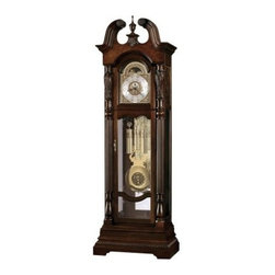 Howard Miller Lindsey Grandfather Clock - Modern construction combines with Old World elegance to make the stately Howard Miller Lindsey Grandfather Clock. This piece features a Cherry Bordeaux finish on a hardwood and veneer base. The matched wood pieces have exquisite details, with olive ash burl, carved rosettes, turned finials, and a hand-rubbed split pediment crown. Reeded columns, elaborate carvings, and embossed molding also accent the exterior. A traditional astrological blue moon phase design complements the bright polished brass dial with cast corners and center ornaments. The intricate face remains easy to read, with applied brass Arabic numerals.This clock is powered by a cable-driven triple-chime Kineinger movement with an automatic nighttime chime shut-off option for your convenience. If you need access to the movement, simply open the locking door. The inner workings of this clock include polished brass weight shells, beveled glass on the side panels, and an illuminated mirrored back. Included adjustable levelers placed under all corners level the clock on uneven or carpeted floors.About Howard MillerBeginning in the 1920's, Howard Miller clocks have impressed all who see them with superior quality and design. Howard Miller wall, floor, and mantel clocks are crafted to last for generations and to perfectly accent your home.The company's founder, Howard C. Miller, began manufacturing wall and mantel clocks in Michigan. Evolving to encompass cabinet making and other furniture design - all renowned for quality and style - the Howard Miller company proudly stands behind its reputation as the World's Largest Clock Manufacturer.