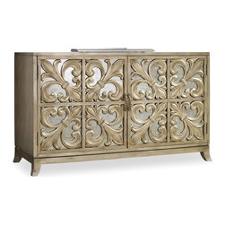 Hooker Furniture - Melange Fleur-de-lis Mirrored Credenza - A metallic fleur-de-lis motif against a mirrored backdrop creates glamour on the Fleur-de-lis Mirrored Credenza.  Two adjustable shelves behind each of two doors.  Ventilated back panel.