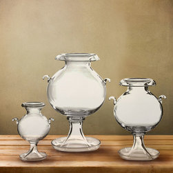 Fishbowl Vase - 18.75 x 13.75 - An unusual and portly form with distinctive details like a turned-back lip, tapered pedestal, and diminutive side handles, the Fishbowl Vase is made from clear glass that makes the stems of your bouquet or the full depth of your selected filler a visible, integral part of its display.  This transitional piece is ideal for angular spaces; its forms defy standard lines.