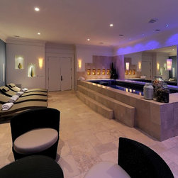 Endless Pools - Original Endless Pools®, Man Cave, Basement Renovation - Sleek, calming, functional. Lit for a peaceful lavender hue over the poolside topiaries and sculpted white waves on the right-side wall, this room can only have one purpose: to pamper yourself silly.
