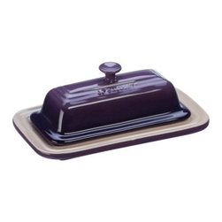 Le Creuset Butter Dish - Cassis - Trust the pros at Le Creuset to come up with another must-have kitchen essential: The Le Creuset Butter Dish - Cassis has a rich purple enamel that looks great on the table and it's crafted of stoneware to retain a cooler temperature longer. It goes from fridge to microwave to dishwasher, beautifully. Durable enough for daily use, resistant to chipping, staining, and cracking, this beauty even comes complete with the signature Le Creuset triple-ring accent, smart handle, and 5-year manufacturer's warranty.About Le Creuset of America Inc.From its cast iron cookware to its teakettles and mugs, Le Creuset is a global standard of inimitable color and quality. Founded in 1925 in the northern French town of Fresnoy-Le-Grand, Le Creuset still produces enameled cast iron in its original foundry. Its signature color, Flame, was modeled after the intense orange hue of molten cast iron within a cauldron (or Creuset in French), and has been a Le Creuset bestseller from the company's first year to the present day.Though best known for its vibrantly colored cookware and original inventions such as the Dutch oven, Le Creuset has also forged a name as a creator of stoneware mugs and enamel-coated stainless steel teakettles. The style and performance of Le Creuset's Cafe Collection and tea accessories are rooted in classic French cookware: bold colors, cylindrical loop handles, unmatched thermal resistance and heat distribution, and of course the iconic Le Creuset three-ring accent. Through its consistent qualities of authenticity, originality, and innovation, Le Creuset maintains a connection to both heritage and modernity.
