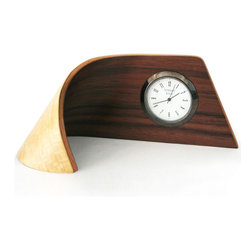 Wood - The curved clock is remarkably created by manipulating exotic woods into this shape. Battery operated and easy to replace.
