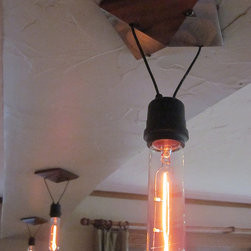 """Handcrafted Lighting - TestTube suspends an exposed T-style bulb from a pyramidal ceiling plate. It is stained and varnished pine in a very nice warm brown color. The socket is a black rubber covered industrial model. The lamp hangs 12"""" from the ceiling to the bottom of the bulb on black vinyl covered wire. This would be the minimum drop but other lengths can be supplied. Please inquire. The 4 1/2"""" square ceiling plate is drilled and supplied with screws that will line-up with the threaded holes found on a standard 4"""" junction box. A 40W bulb is provided and replacements are readily available from Home Depot, Lowes, etc."""