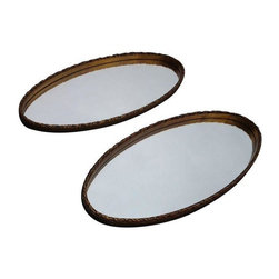 Used Vintage Gold Lead Oval Mirrors - A Pair - This pair of 1960's oval mirrors with carved gold leaf frames would be perfect in a bathroom with two sinks or in the corner of a room. It's all about symmetry! These pieces are in good vintage condition with some wear due to age and use.