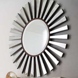 "Horchow - Sunburst Mirror - Retro glamour revisited. Add the ambiance of reflected light to a room with this beveled mirror surrounded by mirrored rays. Imported. Made of wood and mirrored glass. Hooks on back for hanging. 36""Dia. x 3""D."