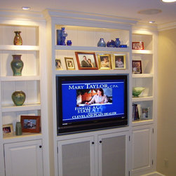Custom Cabinetry - The shelves all have a glass center to allow light to filter down from the top and light up their pictures.
