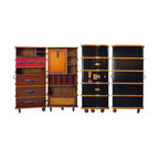 """Black Stateroom Armoire - The black stateroom armoire measures 19.75"""" x 23.75"""" x 51.25"""". Early 19th C. French Louis Vuitton and Goyard trunk and luggage workshops exported to the traveling upper classes of the world. As trunk-making techniques became more advanced, these makers produced virtuoso examples of the French styles. Complete traveling closets were made to accommodate the elaborate dresses, suits, and uniforms of the Belle Epoque. Inspired by originals from the turn of the century, AM introduces a collection of nostalgic but highly practical trunk reproductions. The Armoire features a multitude of shelves and drawers to store and display. Hand-sewn bridle leather straps and brass hardware support a foldout shelf for use as workspace. It opens to a removable, inset shelf-unit with a removable mirror stored in the back. The rattan compartment underneath will hold laundry and shoes. Fun, decorative and practical. Custom made, solid brass hardware. Bridle leather handles and straps. Locks with keys. Seven wood and rubber wheels, of which four will lock."""