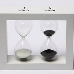 "Contemporary 1 & 3 Minute Sand Timers in White Wood Frame - The contemporary 1  3 minute sand timers in white wood frame measures 5.25""H. The sand timers are made with hand crafted glass globes and are truly stunning. This item is commonly used as an egg and tea timer. The white wood frame is marked with ""1 minute"" and ""3 minutes"" over the appropriate sand timer. The sand timers are filled with white and black sand. This is a very popular item for corporate events and parties. It makes an excellent gift for everyone from the graduate to the executive. Sand timers are aesthetically pleasing ornaments, rather than accurate timepieces. These sand timers are usually accurate to within 1 minute."