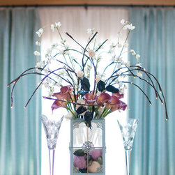 The Firefly Garden - Breakfast at Tiffany's, White Lights - Breakfast at Tiffany's is a playful yet elegant, illuminated experience inspired by the classic film starring Audrey Hepburn. Delicate lighted branches, Calla Lilies and cream silk flowers gently swoon over a vintage glass lantern like a willow tree. This arrangement offers a variety of lighted branch options to suit your personal style or event.