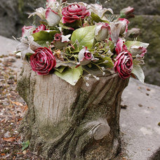 Cement tree stump planter with faux flowers
