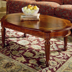 Magnussen Furniture - Oval Cocktail Table - Sedona - Medium brown cherry finish with lightly burnished accents. Constructed in cherry veneers and hardwood solids. Top features an inset border of burled ash. Legs are constructed in a fluted tapered manner with a rosette carving. Shaped ends on oval cocktail and side-matched cherry veneer. Traditional style. Wood top. 48 in. W x 30 in. D x 18 in. H
