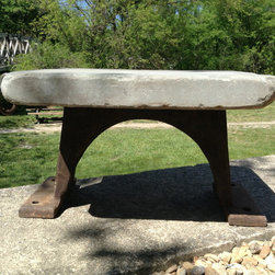 """Inspired Stones Gallery - Built to last with a tumbled bluestone seat and an industrial iron base. The arched base is a picture of grace and compliments the smooth and comfortable seat. An antique iron ring dangles freely from this """"bread board"""" looking, one-of-a-kind bench."""