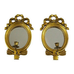Gustavian - Pre-owned Gustavian Style Mirrors with Candlesticks - A Pair - If you're going for that old-world look, this pair of early 1900s Gustavian-style Swedish gilt oval mirrors with bow designs is your answer. Exceptional mirrors that will frame any hallway or room fabulously. Each has a handcrafted brass candleholder attached. Purchased in Stockholm, Sweden. Some minor loss of paint and wear visible.
