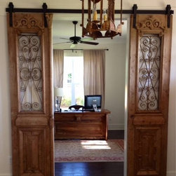 Office - Sliding barn doors, made from antique French iron doors, lead to an office with a large desk custom designed from antique French doors and reclaimed cypress.