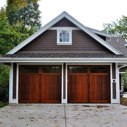 """Carriage House Overlay - C.H.I. Overhead Doors Carriage House Overlay Collection garage door series 5700, with Stockton windows in Western Red Cedar with wrought iron hardware. The boards are backed by a rigid steel base and insulated with 2"""" thick CFC-free polyurethane. Photo by Brian Beachy."""