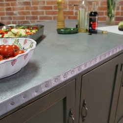"Zinc Top on Kitchen Island - When we thought about the perfect compliment to our farm table and barn wood collection, we all agreed that zinc was a natural progression.  Subtle, elegant and highly durable, zinc is one of the few metal eating surfaces that are food safe and is found in many foods we eat and can be found in every cell of our body.  While we don't suggest you nibble on our tables as a vitamin supplement, we highly recommend this surface for baking, eating , artwork and much much more.   Patinas naturally with age and only gets better with time.  The old wood base on this kitchen island is painted  in Sherwin Williams ""Pewter Green"" has was glazed with a rub thru finish.   Design your own island and call for details.  Size seen:  60″ x 40″ x 36″h"