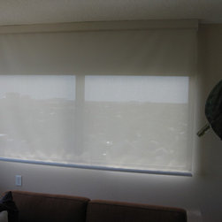 Solar Roller Shades Thru Out Condo - Here in the den, we did two layers again. The solar roller shade in front and a blackout roller shade in back. This window faces west and is the room for watching television. Notice the valance that comes with this line of roller shades. It comes down and under, so if you're looking up, you do not see the roller system. The clean look makes it an architectural feature to the room!