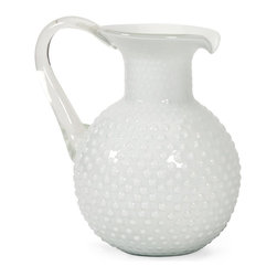 iMax - iMax Simmons Milk Glass Pitcher X-33398 - The Simmons glass pitcher uses a technique first introduced in 16th century Venice. Replicating the process of adding an opacifier to the white glass, this beautiful pitcher mimics a rounded hobnail pattern and features a tapered opening and elegant rounded handle.