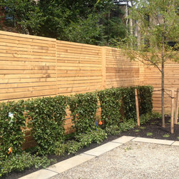 Modern slat fence - Originally created for a small backyard in Logan Circle, DC, this modern fence design features thin, horizontal cedar slats and alternating panels. The slats get progressively skinnier as the fence gets taller.