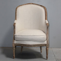 Maison & Co. Antique Highlights - French Louis XVI style chair with a painted wood frame. This barrel-back bergere has a beautifully aged patina and a loose seat cushion. The barrel back extends to upholstered arm pads and curves down to the seat rail. The seat rail is scrolled and supported on tapered, fluted legs. The back legs are splayed. The top rail is scrolled with a central foliate carving. The exposed barrel back frame adds distinct character to the back of the chair.