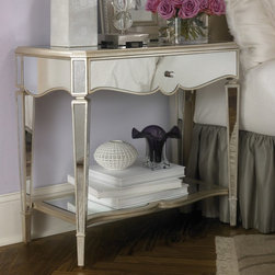 "American Drew - Jessica McClintock Couture Mirrored Silver Leaf 1 Drawer Nightstand - 908-421 - Shop for Nightstands from Hayneedle.com! One of designer Jessica McClintock's most well-known lines consists of elegant eveningwear so it only makes sense she'd offer a line with an equally glamorous way to cap off a black-tie night. The Jessica McClintock Couture Mirrored Silver Leaf Nightstand brings the formal glitz of the ballroom to the bedside with gleaming mirrors and rich detail. And yes it has a bit of practicality too. After all you do need a place to stash your clutch.The nightstand is crafted with a sturdy wood frame covered with reflective mirrors on every aspect accented throughout with glittery silver leaf. Below the spacious tabletop - perfect for a reading lamp and alarm clock - is a roomy storage drawer where you can tuck away glasses hand cream tissues and other nighttime necessities. A fixed bottom shelf provides a home for bulky items such as books magazines and accessories. The scalloped drawer front side panels and shelf along with the four angular tapered legs add a bit of appropriate Art Deco flair - this piece is after all a nod to the age of elegance.About American DrewFounded in 1927 American Drew is a well-established leading manufacturer of medium- to upper-medium-priced bedroom dining room and occasional furniture. American Drew's product collections cover a broad variety of style categories including traditional transitional and contemporary. Their collections range from the legendary 18th-century traditional ""Cherry Grove "" celebrating its 42nd year of success to the extremely popular ""Bob Mackie Home Collection "" influenced by the world-renowned fashion designer Bob Mackie. ""Jessica McClintock Home"" features another beloved designer bringing unique style to an American Drew line. American Drew's headquarters are located in Greensboro N.C. Their products are distributed through thousands of independently owned retailers throughout the United States and Canada and around the world."