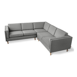 "Gus* - Adelaide Bisectional Sofa - Adelaide Bisectional Sofa   by Gus Modern    At A Glance:   Inspired by the hallmarks of the mid-century movement, the Adelaide Bisectional features structured side cushions and tapered wood legs with a lean silhouette. Gus Modern has designed this sectional sofa to be right or left-facing, according to your needs.  What's To Like:    The Adelaide Bisectional is sophisticated without pushing all the ""fancy-pants"" buttons. You'll be able to impress, your home will look well designed, but you'll avoid that stuffy feeling. ""Urbane"" is a good word for this sofa. The cushions are reversible and easy to switch around, so you'll be able to maintain even wear - especially if you always like to sit in the same spot. Whether you want it in the right or left corner of your living room is up to you. Adelaide will fit in either corner due to its symmetrical design.   What's Not to Like:   The price is steep, but for a sectional of"