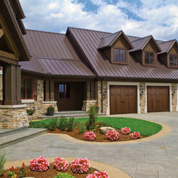 Clopay Canyon Ridge Collection - The dark wood garage doors give the home a more sophisticated look and go well with the roof and rock wall.