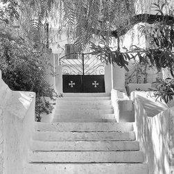 Stairway To Luxury, 8x12, Print - Fine art black and white photograph of concrete and stucco staircase, shaded by dappled light from overhanding trees, which leads to an iron gate. Beyond the gate we catch glimpses of a Greek villa. Location: Greek island of Milos.
