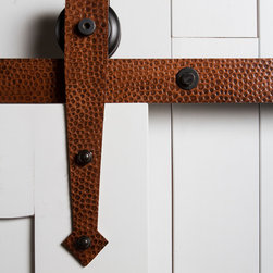 """Barn Door Hardware - A perfect combination of rustic design and old world """"blacksmithing"""" techniques, this Hammered Arrow roller hanger is defined by its hand hammered texture and pointed arrowhead base. The Hammered Arrow roller hanger is designed with a rounded top edge, leaving the wheel exposed and visible as it rolls along the track. This hanger mounts the face of the door."""