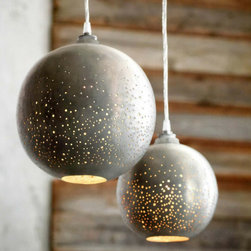 Constellation Pendant Lamps - Stardust sparkles of light glow from our Constellation Pendants.  Globes of zinc-plated iron are hand-drilled to create stellar shades.  The pendants feature clear cords and porcelain sockets.