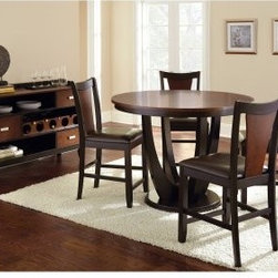 Steve Silver 5 Piece Oakton Counter Height Round Dining Table Set - Black / Ches - You don't need to spend a whole Saturday searching through antique malls to get that retro-modern look - it's right here in the Steve Silver 5 Piece Oakton Counter Height Round Dining Table Set - Black / Chestnut. Crafted of wood, this collection has a savvy two-tone black and chestnut finish. The table has a bold sculptural base, while the chairs feature cutout chair backs and cozy black vinyl upholstered seats. Order yours today - and skip the antique hunt.About Steve SilverSince its founding in Forney, Texas, in 1987, the Steve Silver Company has had a simple focus: to provide the best quality product at an irresistible price, back it up with uncompromising service, and continue to improve every day. As one of the premier suppliers of dining sets and occasional furniture in the country, Steve Silver is proud to make you, the customer, its top priority, utilizing state-of-the-art equipment, proven operating procedures, and over 500,000 square feet of facilities. You'll feel equally proud displaying furniture from the Steve Silver Company in your home.