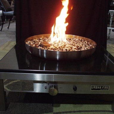 """Fire Pits - Great for Fall and Winter - The Urban Fire II is a contemporary looking 304-grade stainless steel outdoor gas fire pit suitable for residential and commercial locations. This all-weather fire pit uses glass to create a """"dancing fire"""" flame that also acts as a heat source on cool evenings. The fire light reflects off the safe-to-touch glass creating a relaxing atmosphere. while the included protective cover turns the fire pit into a functional outdoor coffee table."""