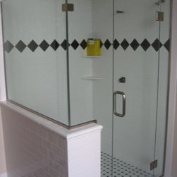 """Framless Return Shower Doors with Knee Walls - Lead panel is secured with a through-the-glass support bar to stabilize the weight and swing of the door. The door is attached with 180 degree glass to glass hinges. Panel to the left of the door is notched to create a ledge on the inside of the shower enclosure with a return panel that sits on a knee wall. ½"""" glass with brushed nickel hardware."""