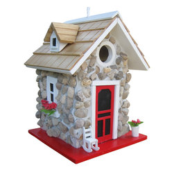 """Home Bazaar Inc. - Fieldstone Guest Cottage - Stone - This quaint stone cottage has a pine shingled roof and features a sturdy, river stone façade as well as a window box and flower pot with bright red flowers. We've topped it all off with a white trimmed, red door detail and a white rocking chair. The 1 ¼"""" opening is designed to accommodate nesting birds such as wrens, finches, chickadees and nuthatches.  The house has all of the qualities for a birding enthusiast including a back wall cleanout, drainage, ventilation and an unpainted interior. Loop the heavy duty nylon cord to the desired height and put this house where flying visitors will find it."""