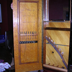 """Repurposing Piano Parts - Jewelry cabinet made from 100 year old Lester """"Cabinet Grand"""" piano.  On the inside of the door are piano wires for hanging earrings.  Below that are spring loaded string dampers used to clamp jewelry to the black velvet panel.  Inside the cabinet are mirror, LED lights, a tray made from the curved keyboard cover, felt covered pegs to hang necklaces and a sectioned tray at the bottom.  The hammers are arranged in a fern shape."""
