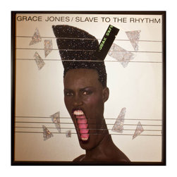 """Glittered Grace Jones Slave to the Rhythm Album - Glittered record album. Album is framed in a black 12x12"""" square frame with front and back cover and clips holding the record in place on the back. Album covers are original vintage covers."""