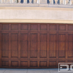 Dynamic Garage Door - California Dream 18   Custom Designed Wooden Garage Door in a Raised Panel Style - Wooden trim pieces can be arranged in countless design patterns that result in extraordinary custom designs. This Cedar Wood Garage Door's trim pattern is uniquely arranged and the routered edges simply make it look grand in unique design and quality. Master stained and coated with a satin clear finish this garage door will look great for many years to come. It is a garage door that definitely has marked a trend within the California Beach Community it was installed at.