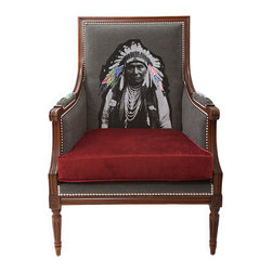 INUKT.COM - Wigwam armchair - This isn't your usual wingback chair, that's for sure.  It showcases a black and white print of a First Nations man's determined face that is rendered edgy with embroidered feathers in pop art colors. With a printed quote on the back, the chair is just as interesting and compelling from this side.  The grey flannel composition and the burgundy cushion, which  is reminiscent of theater-style curtains, are enhanced by gleaming silver studs that outline the silhouette in dark beech wood. All in all, this revisited classic is a definite statement piece.