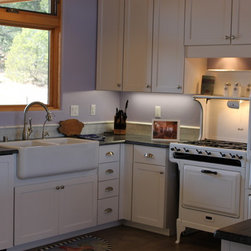"Camony Home by Altair Homes - We paneled the dishwasher so it would blend into the cabinetry.  The Rohl FireClay single bowl Farm sink was scribed in the sink base cabinet for a perfect fit!   Centering the sink under the window prevented the use of a Super Susan cabinet in the corner.  We used a Blind base cabinet but had roll out trays installed so they could be pulled to the door opening.  The items stored in the corner were easily accessible.  The bottoms of the upper cabinets were recessed to accommodate the under cabinet lighting.  The full overlay doors were adjusted to cover the frame of the recessed area.  The valance at the light cover the hood liner, blower, and recessed lights.  The wall cabinets were 30"" high with two layers of 3/4"" filler as crown."