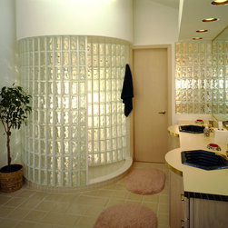 Circular Walk-in Shower - doorless glass block shower with two curved walls providing privacy accompanied with a glass block partition