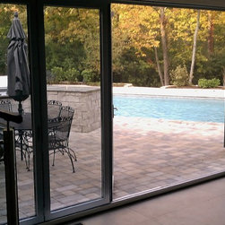 Mirage Motorized Screen With NanaWall System - Mirage motorized screen on inside of house with NanaWall sliding door system overlooking beautiful outdoor pool area. Screen operates at the touch of a button and completely recesses into a custom built wood cavity when not in use.