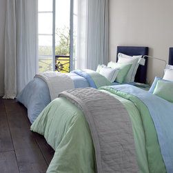 Yves DeLorme Fall Bedding - Transparence, from Yves DeLorme, is a printed on egyptian cotton percale that was designed to coordinate with the three Lola patterns. On one side is a water coloured thin stripe; on the other is a more watercoloured flat effect.  Available in blue or green. Duvet and shams reverse from stripe to flat.  Fitted is also flat pattern.
